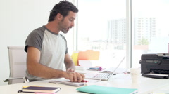Man Working At Desk In Design Studio Answering Phone Stock Footage