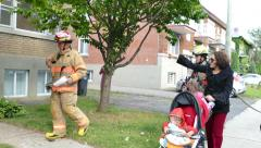 Mom with babies show direction of fire to first firemen to arrive on scene Stock Footage