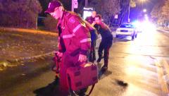 Rescue crews carrying a stretcher forward while doing CPR on trauma victim Stock Footage