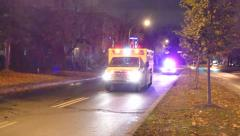 Ambulance with lights followed by police car with camera tracking motion Stock Footage