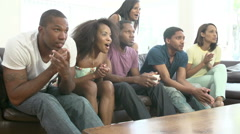 Group Of Friends Sitting On Sofa Watching TV Together Stock Footage