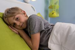 ill child lying in hospital bed - stock photo