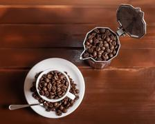 coffee cup and percolator full of coffee beans - stock photo