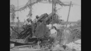 Military soldiers firing 6-inch gun under canopy Stock Footage