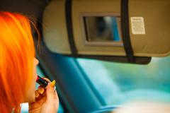 girl painting her lips doing makeup while driving the car. - stock photo
