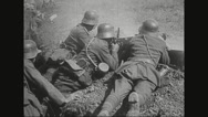 Soldiers firing machine gun while lying in battlefield Stock Footage