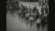 Prisoners walking while carrying wounded person on stretcher Stock Footage