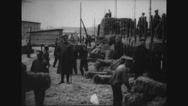 Prisoners carrying hay bales in prison camp Stock Footage