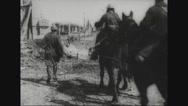 Military soldiers riding horse cart in ruined village Stock Footage