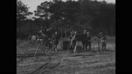 Soldiers setting up and testing 3-4 inch anti-aircraft gun and meter on tripod Stock Footage