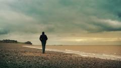 Man Walks Along Sunset Beach Stock Footage