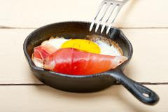 egg sunny side up with italian speck ham - stock photo