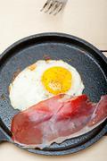 Egg sunny side up with italian speck ham Stock Photos