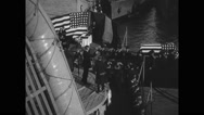 Flag-draped casket being carried by soldiers towards ship Stock Footage