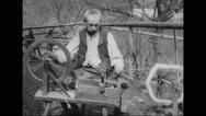 Man spinning thread on wheel Stock Footage
