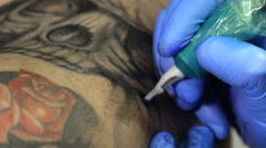 Tattoo artist tattooing a skull Stock Footage