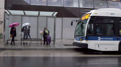 Busstop People Waiting Raining Umbrellas Bus MTA NYC Transportation NYC Stock Footage