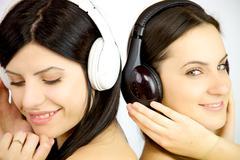 two women enjoying music happy - stock photo