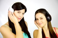 two young women listening music with headset - stock photo