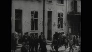 People standing against building with bullet marks in Nancy Stock Footage