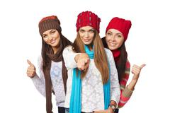 Three girls showing approving gestures pointing at camera Stock Photos