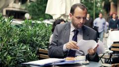 Stock Video Footage of Young businessman comparing, checking documents sitting in cafe HD