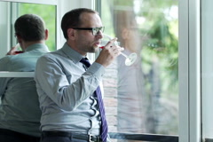 Attractive businessman drinking red wine standing by the window at home NTSC Stock Footage