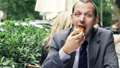 Portrait of happy businessman eating sweet bun sitting in cafe HD Stock Footage