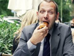Portrait of happy businessman eating sweet bun sitting in cafe NTSC Stock Footage