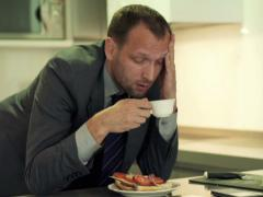 Tired businessman having headache and drinking coffee in the kitchen NTSC - stock footage