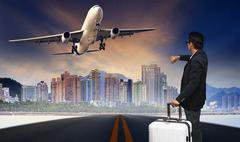 Man with big luggage standing on raod and watching to airplane flying over ur Stock Photos