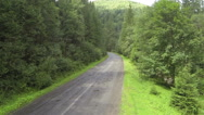 Stock Video Footage of   Up over wood in  mountain with road . Aerial  shot