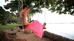 Woman on a swing at palm tree and talking by phone. Koh Samui, Thailand. HD. Stock Footage