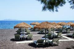 The beach with black volcanic stones at santorini island, greece Stock Photos