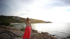 Young woman standing on a rock beach and rises hands. Flying airplane in the sky Stock Footage