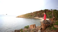 Young woman standing on a rock beach and rises hands. Koh Samui. Thailand. Stock Footage