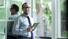 Portrait of happy businessman with tablet computer standing by the window  HD Stock Footage