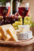 Cheese with a bottle and glasses of red wine on wooden table Stock Photos