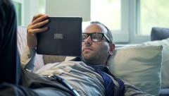 Businessman reading article on tablet computer and drinking beverage on sofa  HD - stock footage