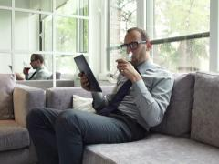 Businessman reading article on tablet computer and drinking wine on sofa NTSC - stock footage