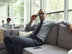 Portrait of happy businessman raising toast and drinking red wine on sofa NTSC Stock Footage