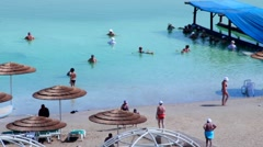 People taking solt water  treatment on the hotel beach at Dead sea Stock Footage
