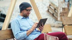 Hipster man using tablet computer while sitting on bench in the city HD Stock Footage