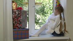 Child with gift boxes and toy in hands looking out the window Stock Footage