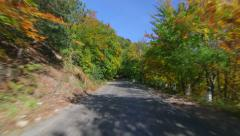 Driving on twisting mountain road through colorful forest in autumn Stock Footage