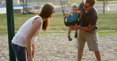 Young family - married couple with baby in park playground. 4K - stock footage