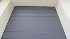 Automatic garage door roll up on tracks across the ceiling Stock Footage