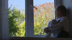 Little girl sitting on windowsill and looking out the window Stock Footage