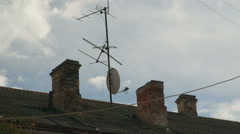 Satellite dish and tv antenna mounted on roof of an old house Stock Footage