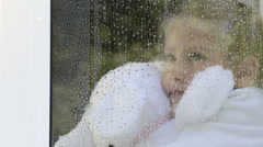 Little girl hugging stuffed toy looking out window in the rain Stock Footage